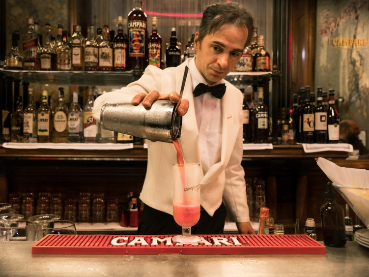 Bartender pouring a drink out of cocktail mixer