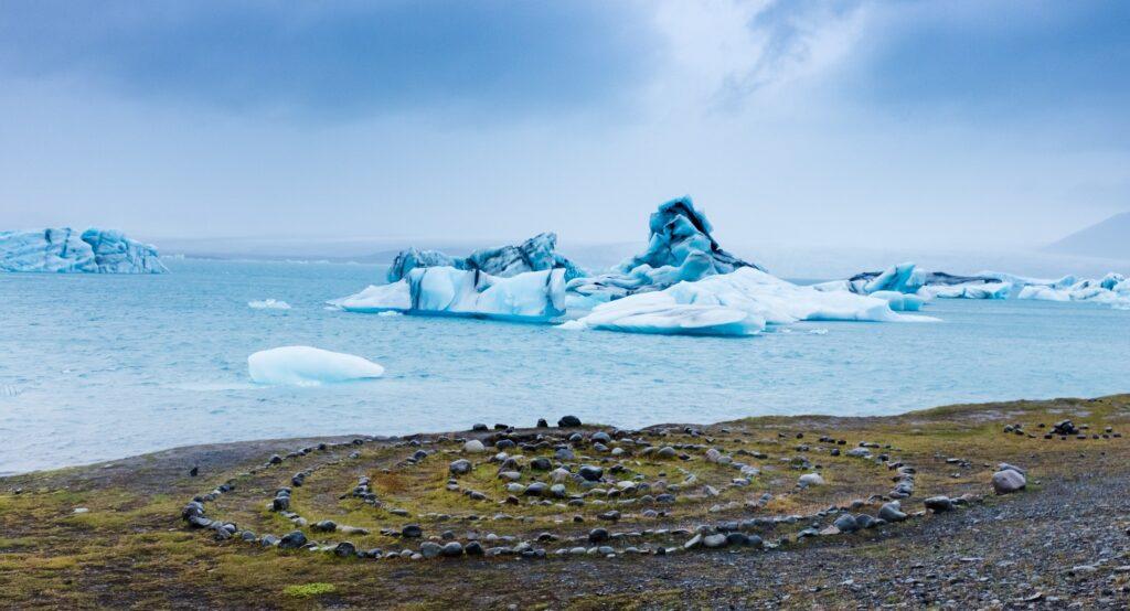 beautiful vista of stones arranged on a shore overlooking blue icebergs