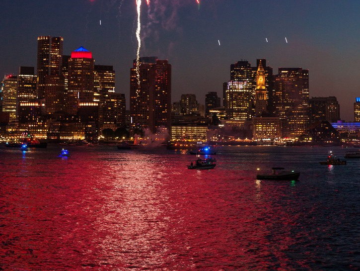 Boats in Boston Harbor glow in the light of an exploding firework.