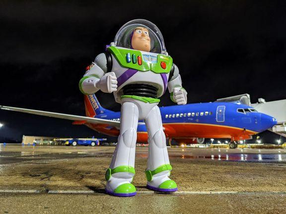 Buzz Lightyear exploring near a Southwest plane.