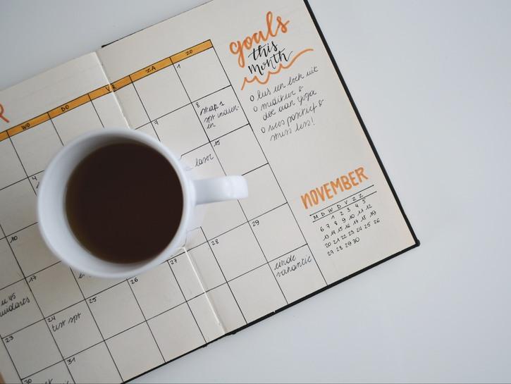 Calendar with a coffee mug on top.