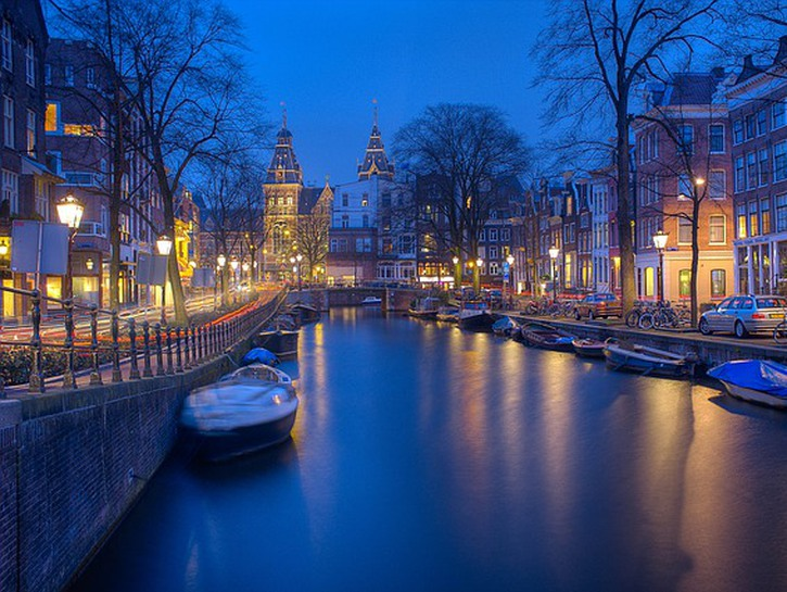 Canal of Amsterdam at night, lined with boats
