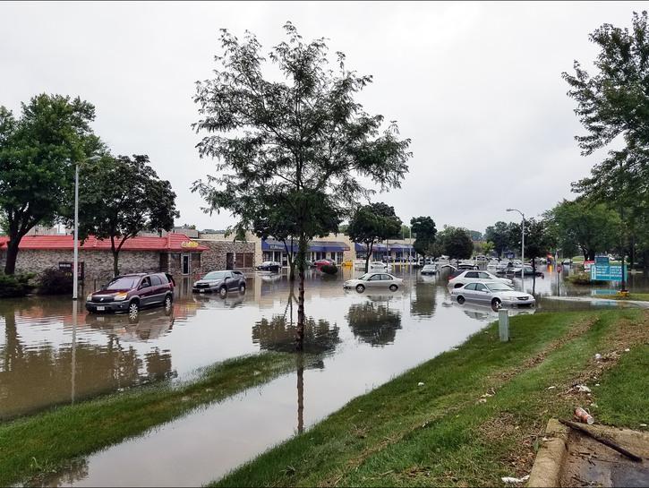 Cars littered across a flooded street