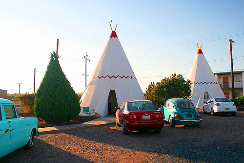 Cars parked outside teepees at the Wigwam Village Motel.