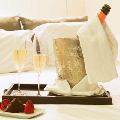 Champagne and chocolate covered strawberries in a hotel room.