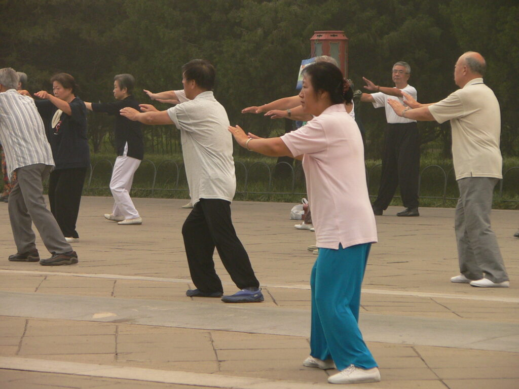 Chinese people practice Thai Chi in public.
