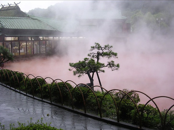 Chinoike Jigoku, blood red thermal spring with steam rising from its surface, Beppu, Japan.