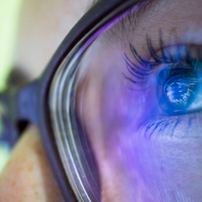 close-up person's eyes in glasses reflecting computer screen
