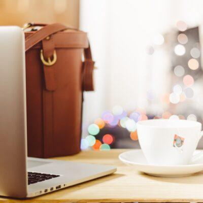 coffee mug and laptop with bag on desk