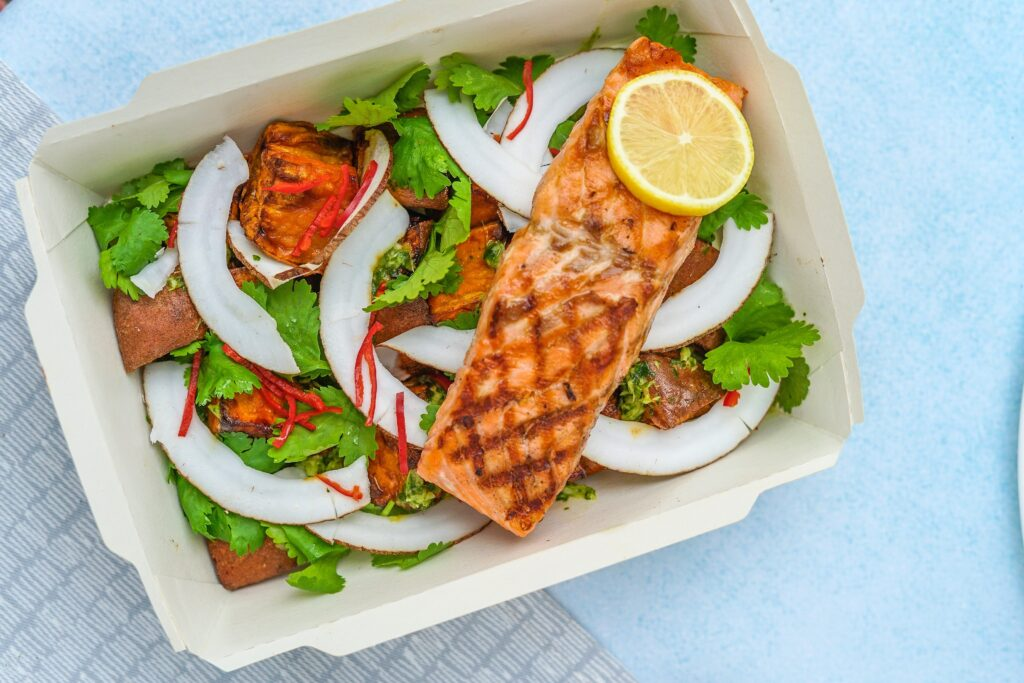 Container of take away salad with salmon