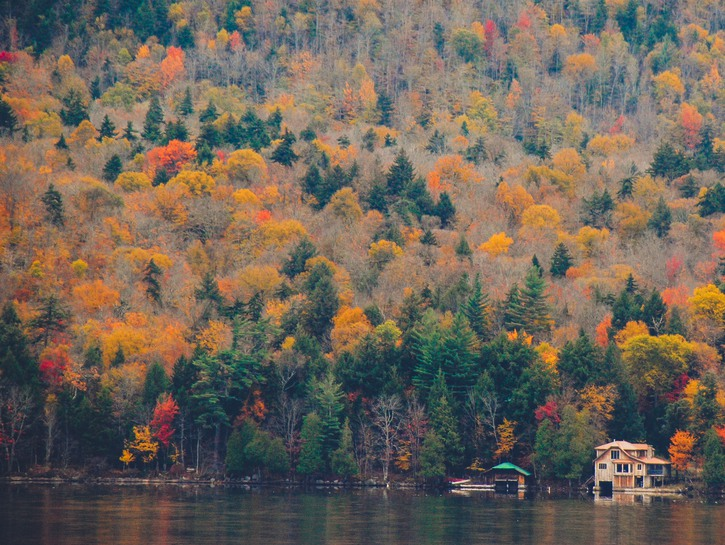 Cottages on lake, with hill of fall trees, the Adirondacks, New York