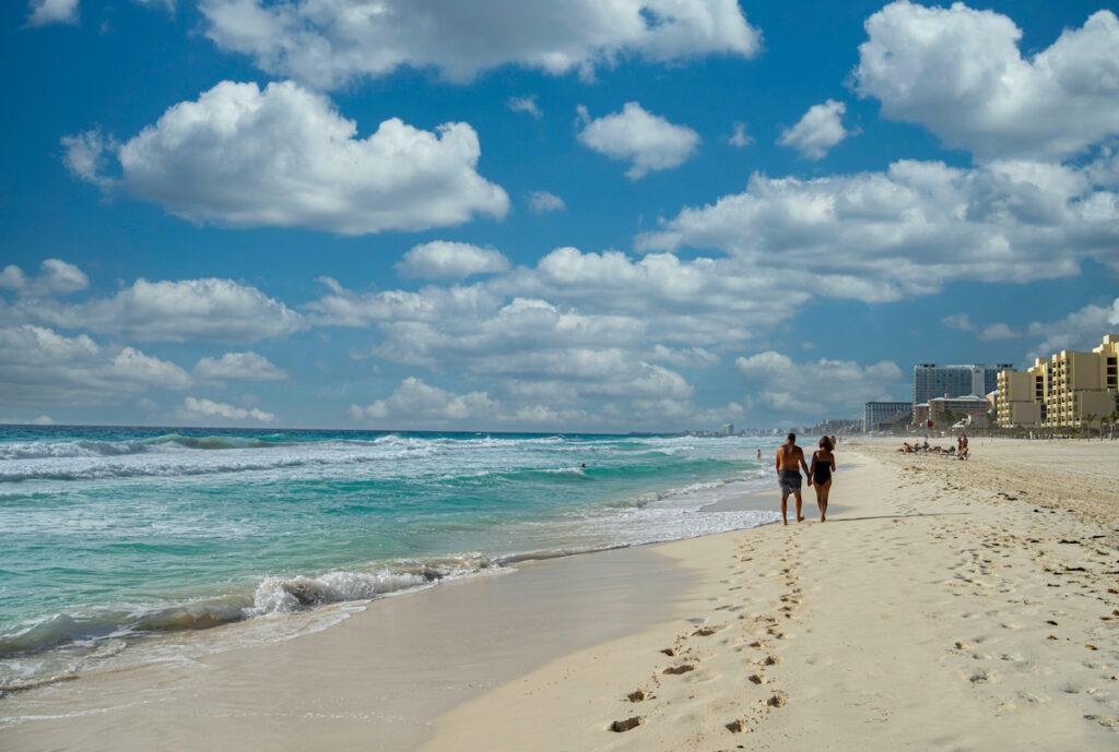 Couple walking on beach, Cancun, Mexico.