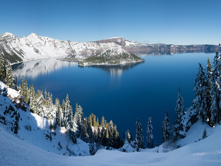 Crater Lake, Oregon, lined with snow and evergreen trees