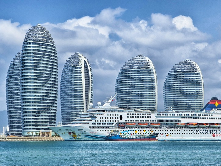 Cruise ship passes in front of modern apartment buildings, China