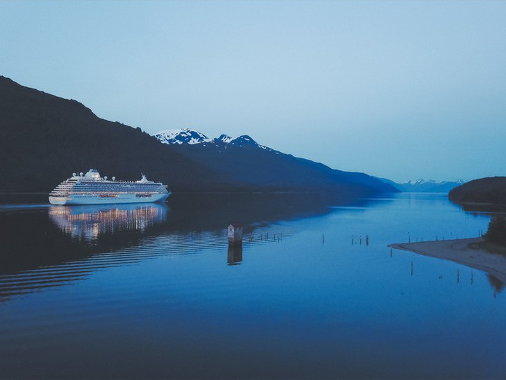 Cruise ship sailing up river flanked by mountains, Alaska