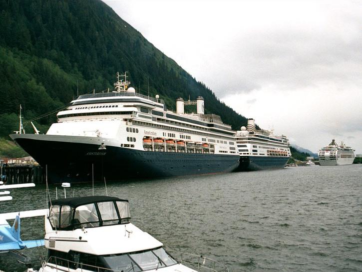 Cruise ships moored at peer beside tree-covered mountain, Alaska