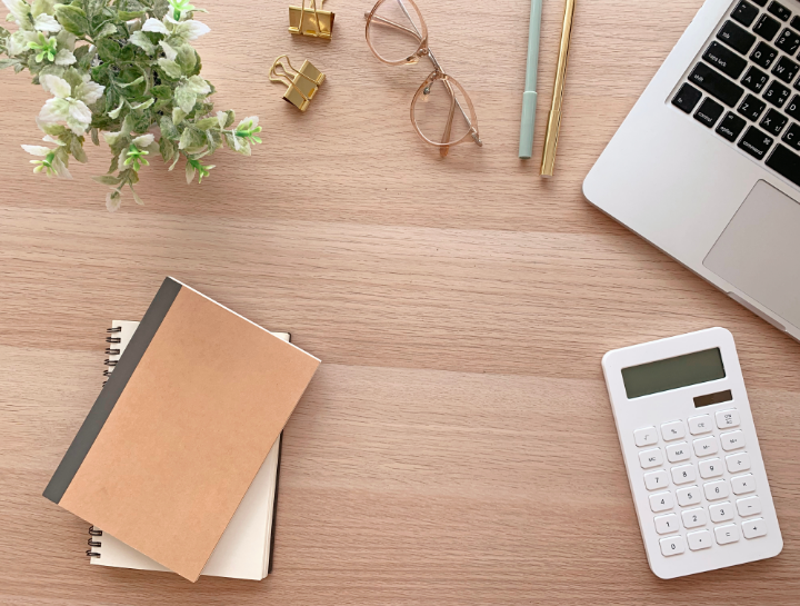 desk surface with notepads, plant, clips, glasses, pens, a calculator, and laptop