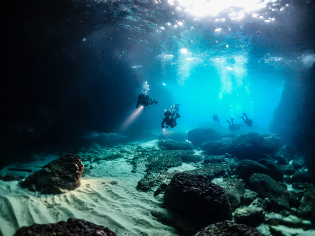 Divers in sea caves off the coast of Malta.