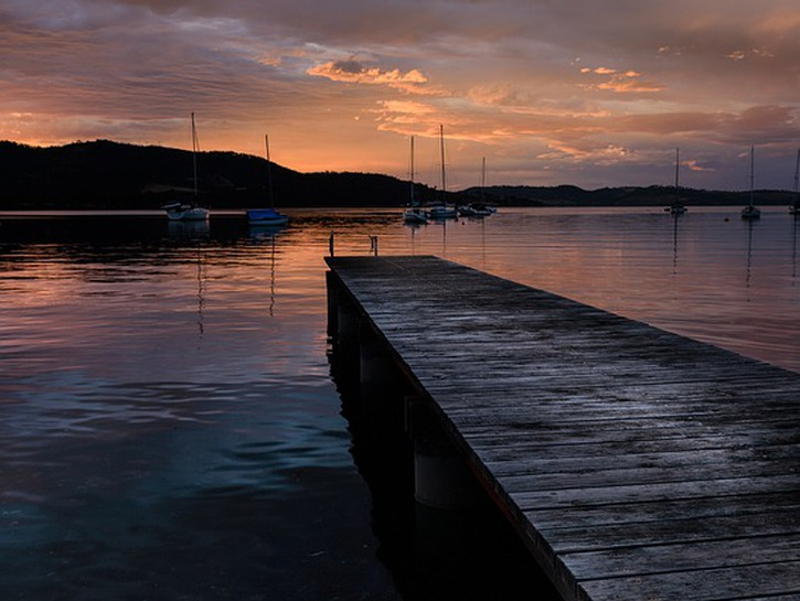 Dock in a Tasmanian harbour at sunset, with ships