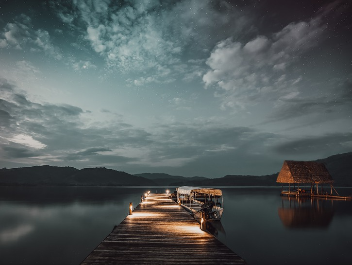 Dock with lights over calm lake at night, mountains in distance, clouds in the sky