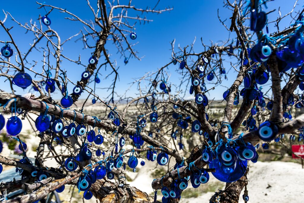 Dozens of blue glass evil eyes hung in the branches of a tree in Turkey