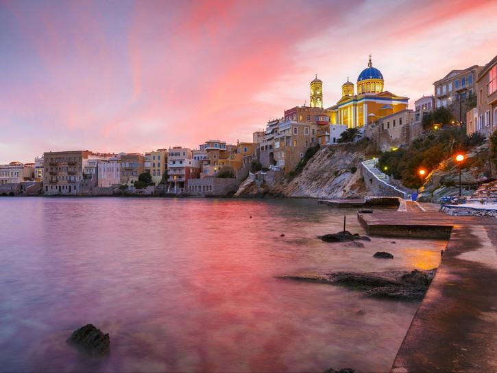 Ermoupolis, Syros, Greece, houses and church on coast at sunset.