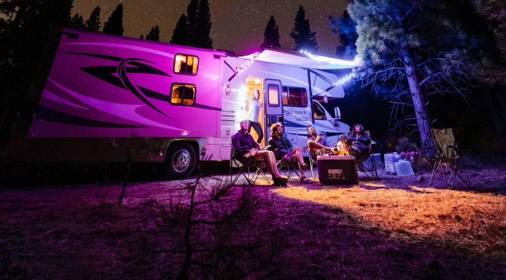 family sitting outside of RV camping at night