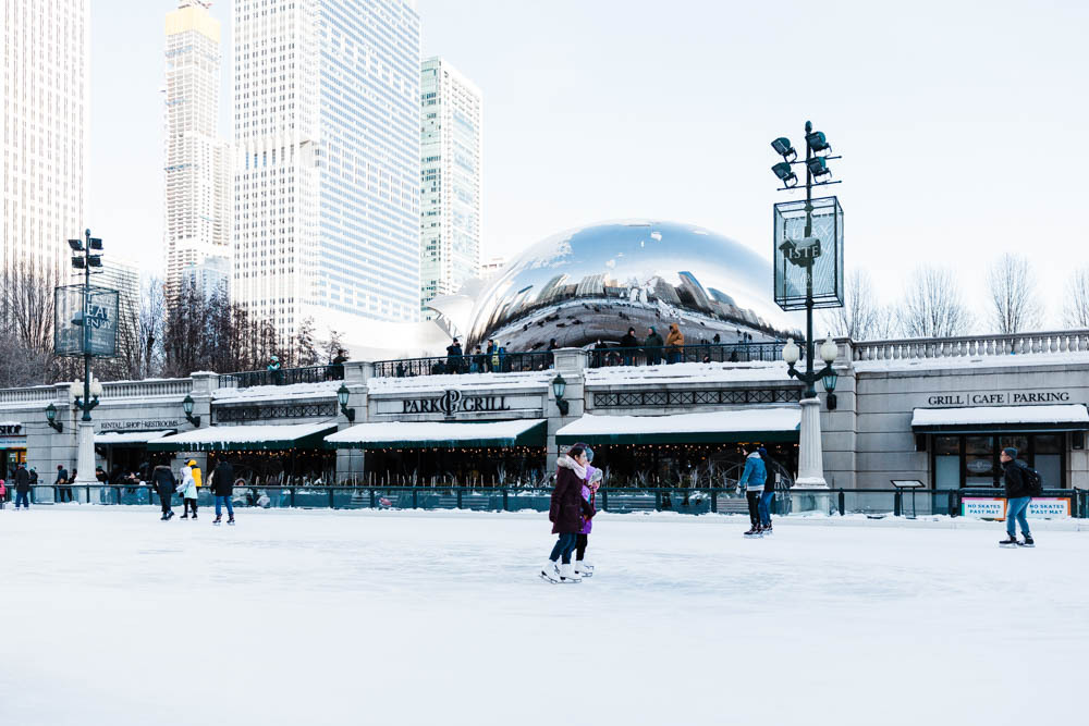 Figure skaters near the Chicago Bean during winter.