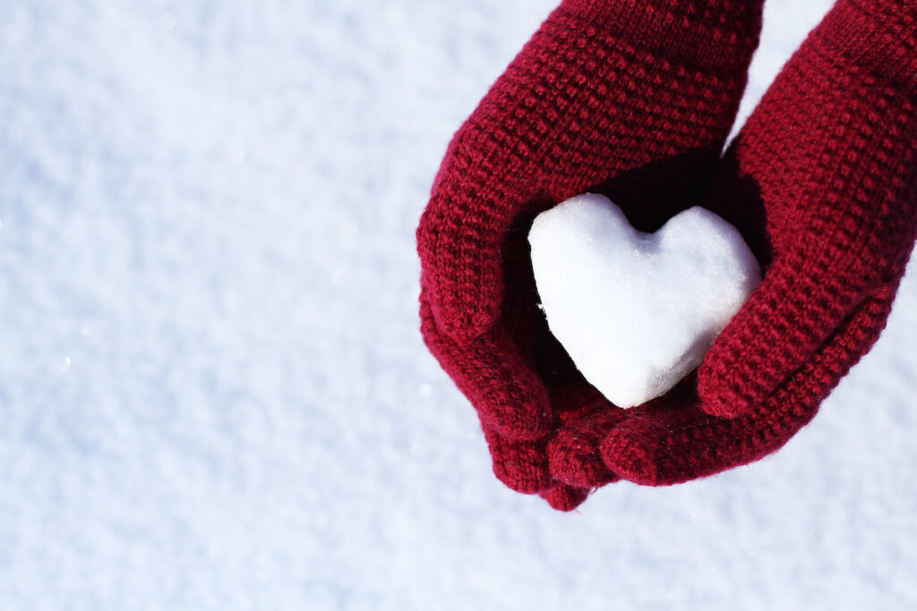 Gloved hands holding a heart-shaped snowball.