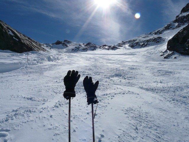 gloves on ski poles on a mountain