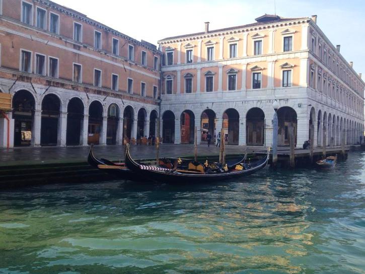 Gondolas rest in the canal near a pier, Venice