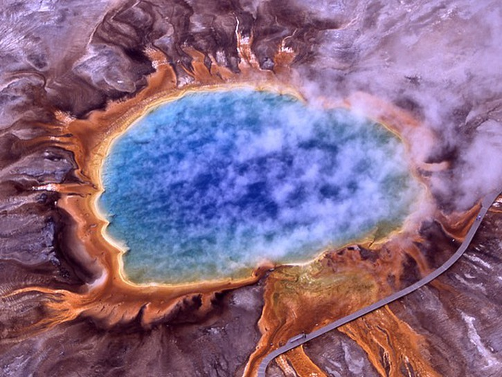 Grand Prismatic, blue and orange thermal spring with rising steam, seen from above.