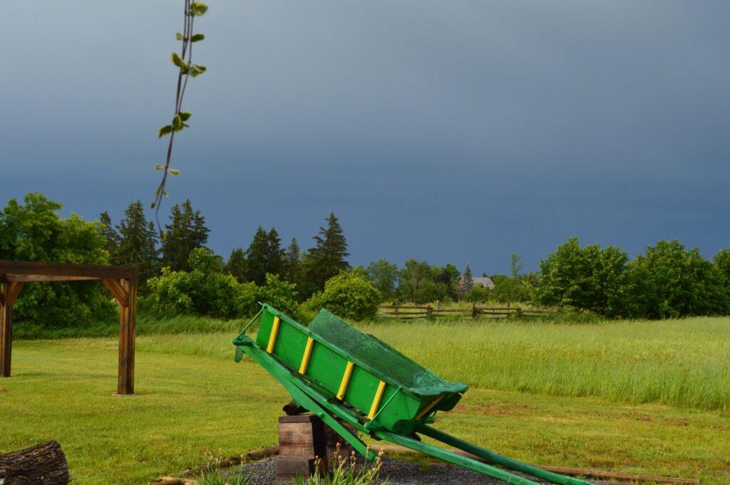 Green farm cart sits in a field as a storm rolls in.