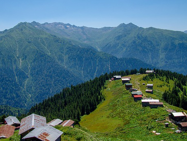 Green hillsides of mountains in Rize, Turkey, with huts and shacks.