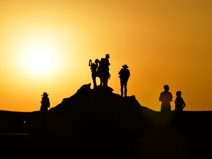 group of travelers silhouette on a hill