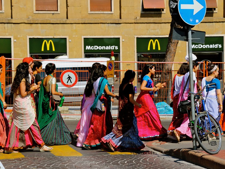 Group of women in Indin dress walk past McDonald's in Florence