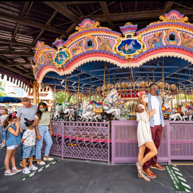Guests at Disney World wearing masks and social distancing.