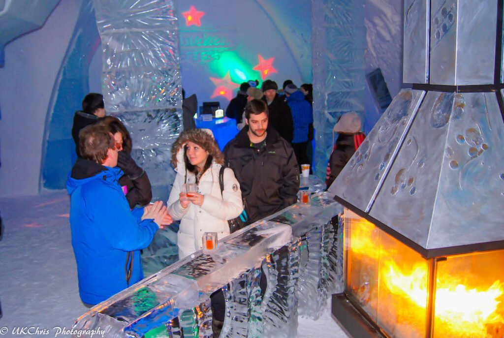 Guests staying warm by a fire at the Hotel de Glace.