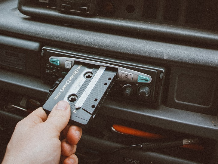 Hand pushing tape into car tape player