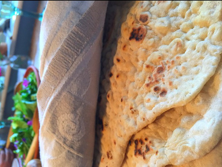 Homemade flatbread sits wrapped in a grey tea towel