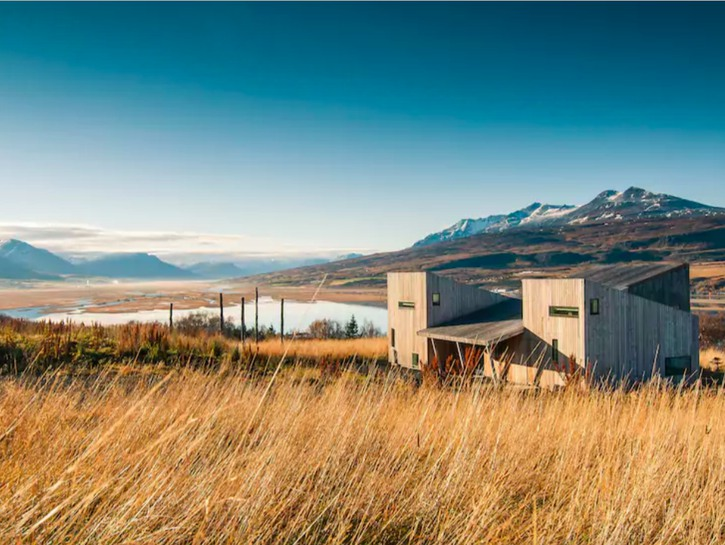 House near Akureyri, Iceland, bay and mountains in background.