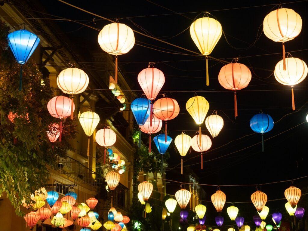 Illuminated, multicolored lanterns over a street.