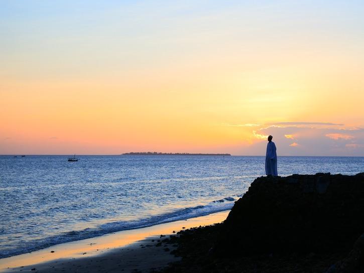 Imam watches sunset on the ocean, Zanzibar.
