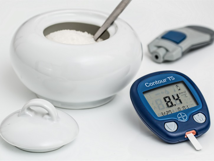 Jar of sugar and diabetes blood sugar tester