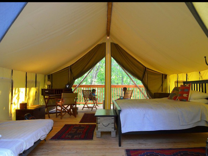 Kids sitting on the balcony, seen from inside luxury glamping tent
