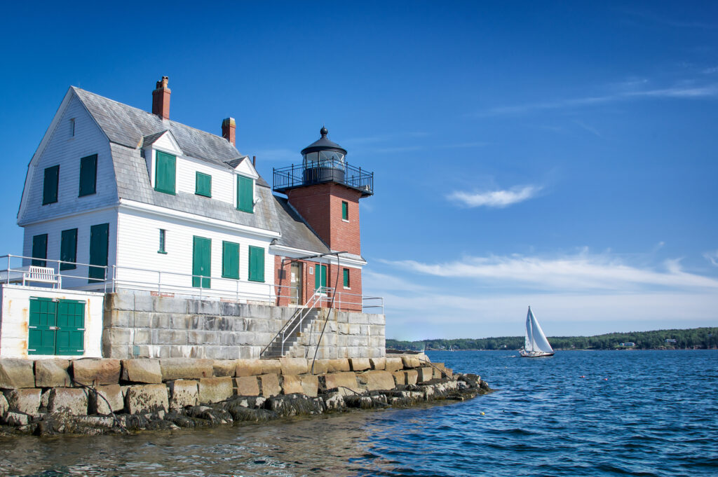 Lighthouse and sail boat in Rockland, Maine.