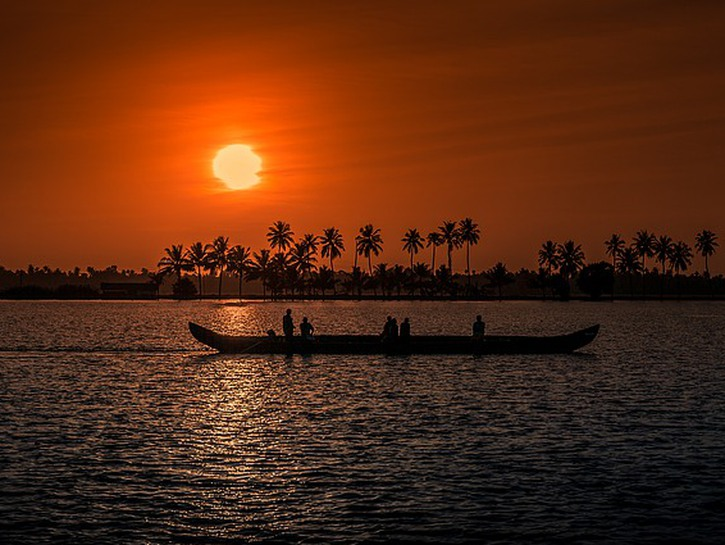 Long boat in the river at sunset, Kerala province India.