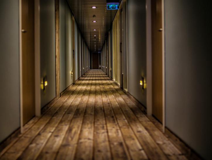 Long hotel corridor featuring wide plank wooden floors.