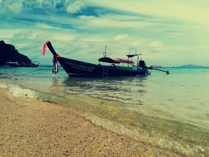 Long-tail boat on beach, Thailand.
