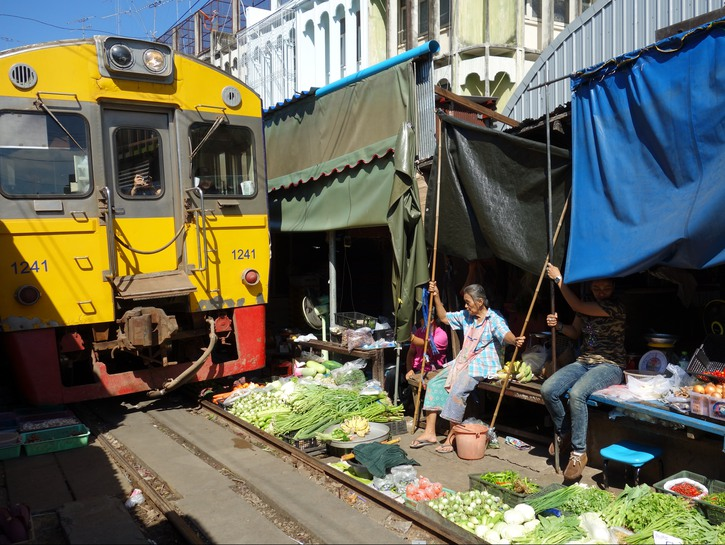 Maeklong Railway train passes through market
